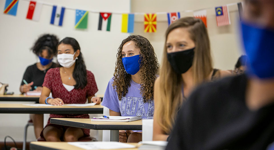 Masked students in a classroom listening to the instructor