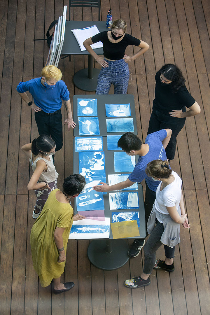 Students in Shambhavi Kaul's Advanced Visual Practice course discuss their cyanotypes, while masked, outside the Ruby.
