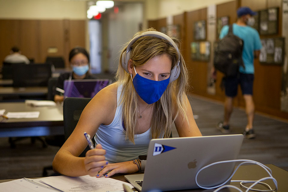 A masked student participates in her Discrete Mathematics for Computer Science via Zoom in Perkins Library.