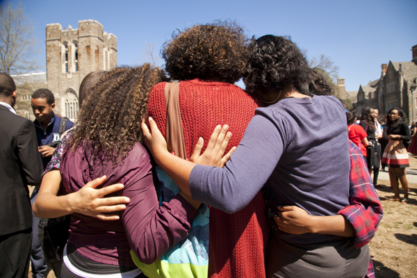 Students embrace in a gathering at the West Campus bus stop.