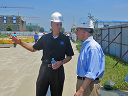 Duke's Kyle Cavanaugh, left, vice president for administration, and Michael Schoenfeld, right, vice president for public affairs and government relations, discuss DKU during a visit to the DKU construction site.
