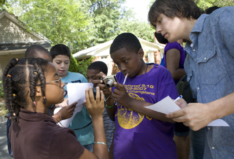 Duke student Casey Dunn, right, watches as Deja Cooper, 13, left, and Kendall Clark, 13, center, use a GPS unit and camera to recording the coordinates of a house while on a walking tour through Walltown.