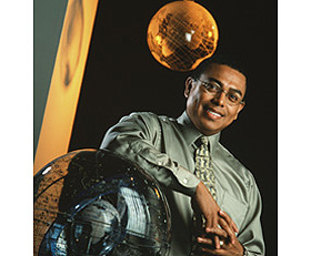Professor Arlie Petters poses with a model of the solar system