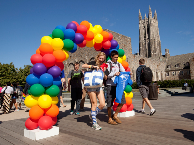 Image of students passing under rainbow balloon arc on Duke campus