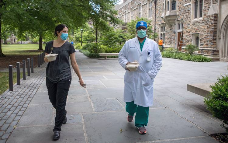 Wearing masks, trauma and critical care surgeons Amy Alger and Suresh Agarwal pick up lunch at Ginger + Soy in the Brodhead Center. Photo by Jared Lazarus, Duke University Communications.