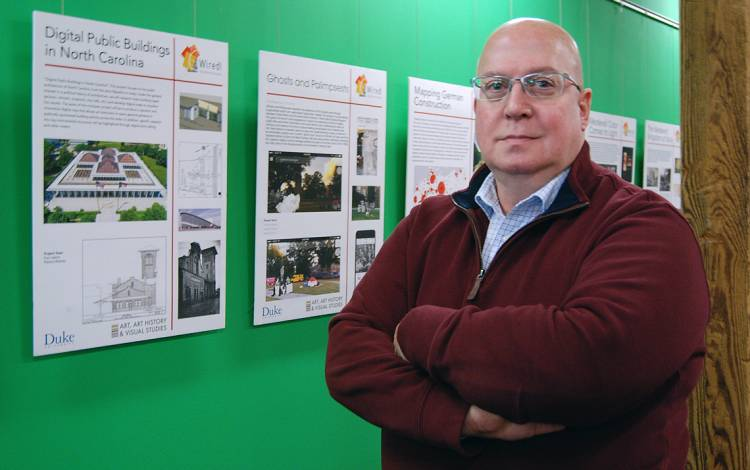 John Taormina standing in front of a green wall.