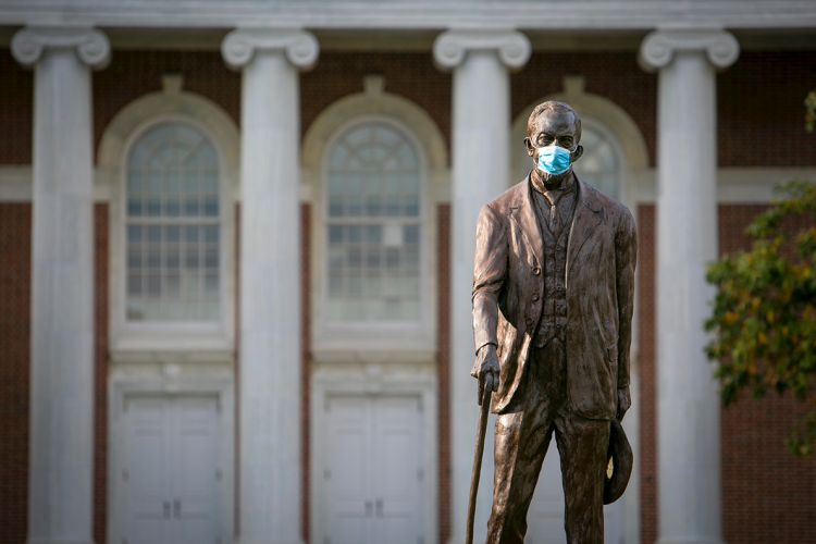 Statue of Ben Duke on Campus wearing a mask
