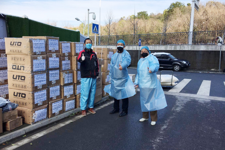 Health professionals at Tongji Hospital of Huazhong University of Science and Technology in Wuhan accept a delivery of quick-dry clothing arranged by Duke Kunshan students