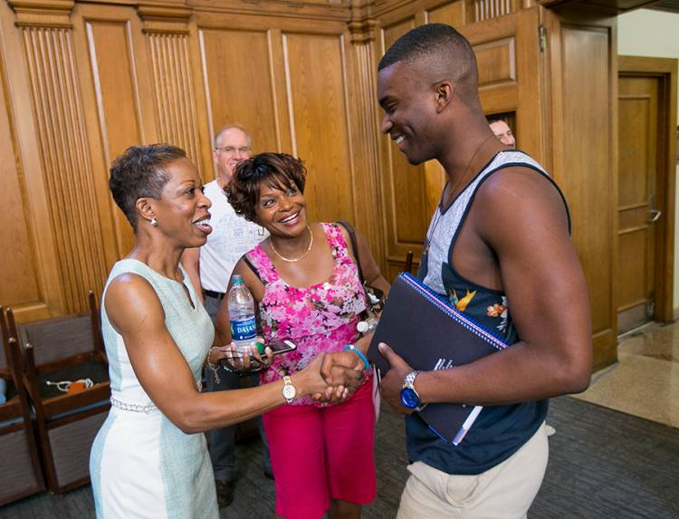 Trinity College Dean Ashby, left, welcomes Denise Lewis, center, and her son, Bryant Lewis, right, during move-in Tuesday. Photo by Megan Mendenhall