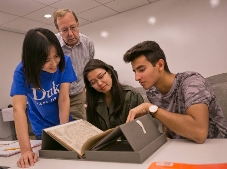Professor Tom Robisheaux looks on as FOCUS students examine a book from the Renaissance. Photo by Megan Mendenhall/Duke Photography