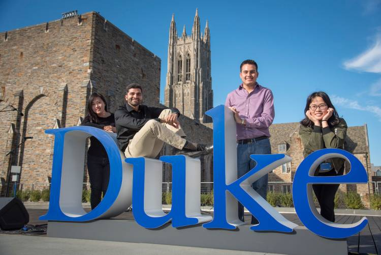 Students pose with the Duke Word Mark on the Plaza Thursday.
