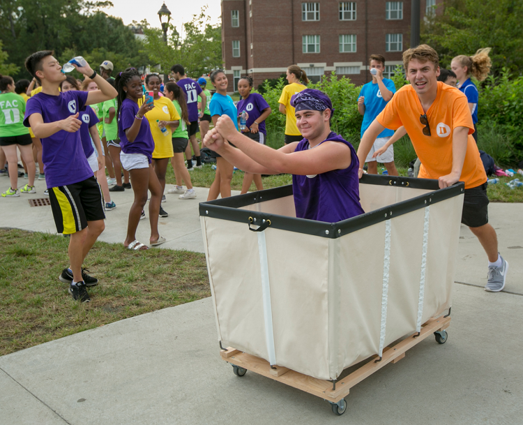 First-Year Advisory Counselor students Sam Dale and Jonathan Suna return with a bin to help move in first-year students at Trinity dorm on East Campus Tuesday. Photo by Jared Lazarus