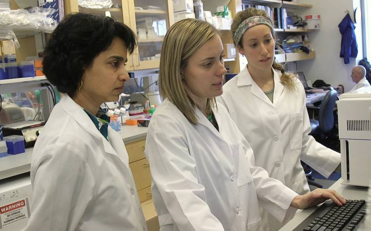 Dr. Smita Nair, left, working in the lab with colleague researchers. Photo by Shawn Rocco/Duke Health