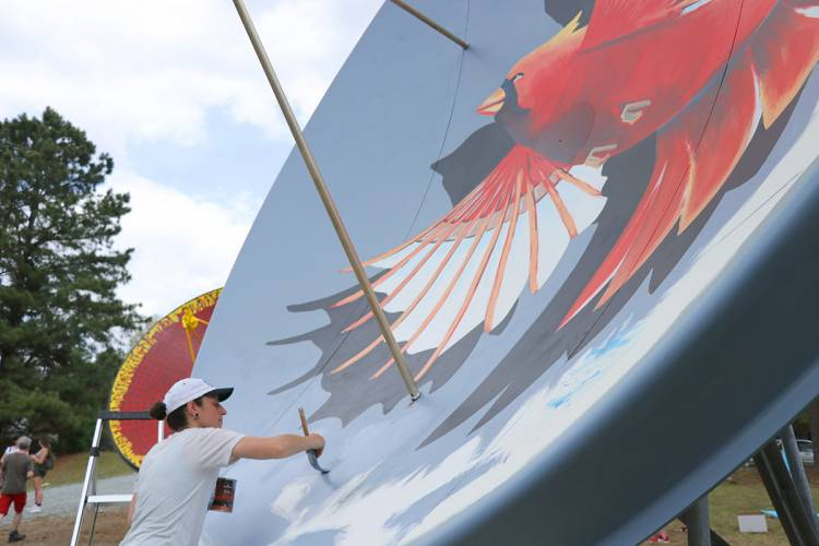 Artist works on a mural of a cardinal.