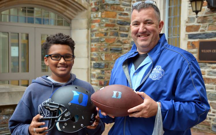 Johnathan Hill, left, and his father, Kevin Hill, show off the helmet and football they got at Friday's Duke Athletics Surplus Sale.