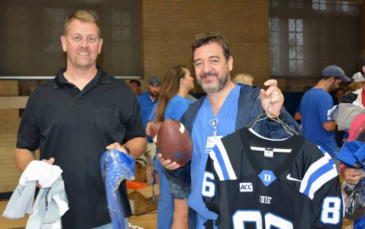 Dickson Clifford, left, and Kent Dixon wait in line at Friday's Duke Athletics Surplus Sale.