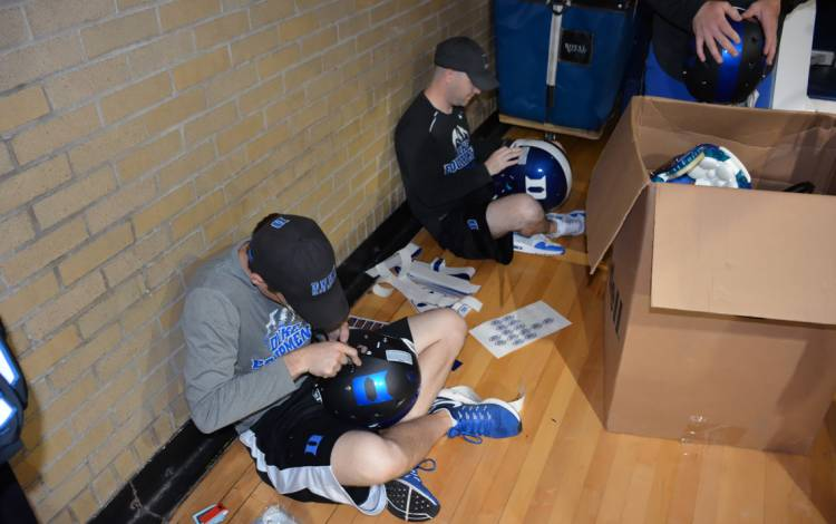 Duke equipment operations staffers Chris Woolsey, left, and Wes Pickell get helmets ready for customers at Friday's Duke Athletics Surplus Sale.