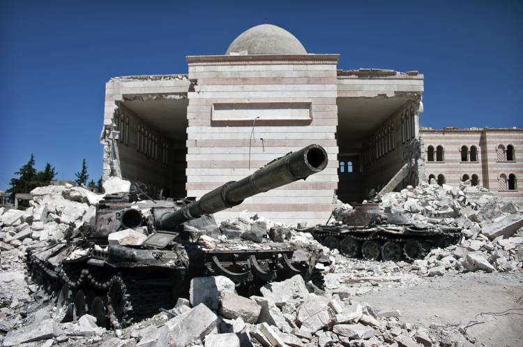 Two destroyed tanks in front of a mosque in Azaz, Syria, August 2012. Photo courtesy of Christiaan Triebert, Wikimedia Commons.