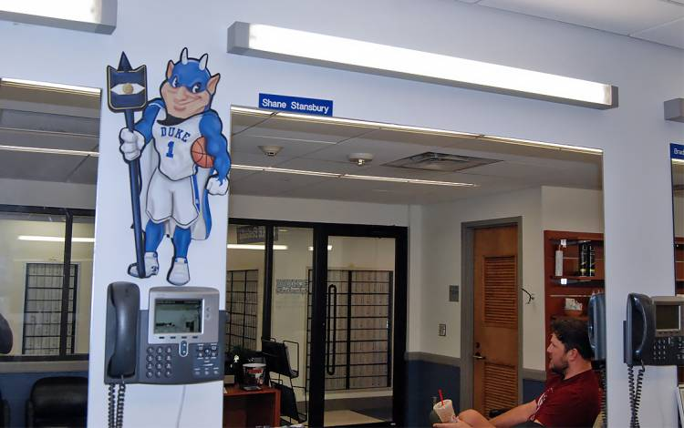 Barber Brad Geercken sits in the shadow of a cutout of the Blue Devil mascot.
