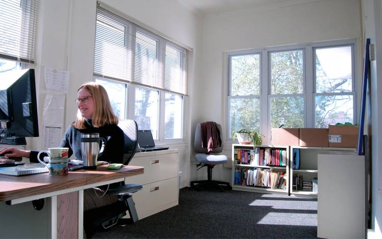Barbara Thompson, an IT analyst with Duke Continuing Studies, works on a converted porch on the second floor of Bishop's House. Photo by Stephen Schramm.