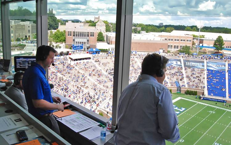 David Shumate, the director of broadcasting for the Blue Devil IMG Sports Network, calls a game from the radio booth at Brooks Field at Wallace Wade Stadium.