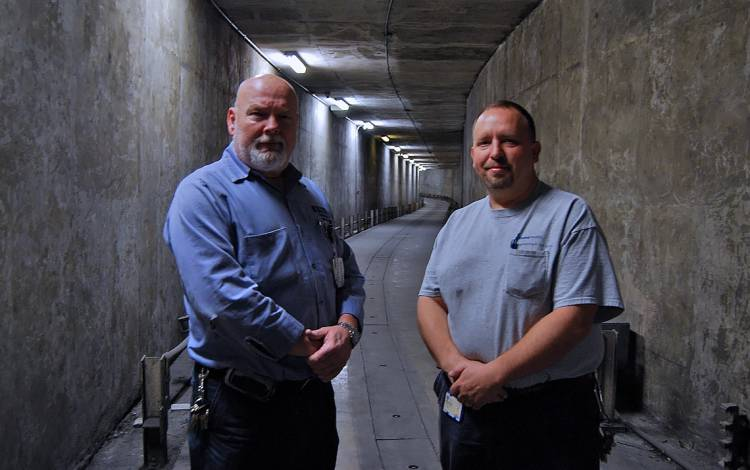 Former members of the PRT team, Eric Brewer, left, and Chris Sutton, right, stand in the tunnel through which the rail system used to run.