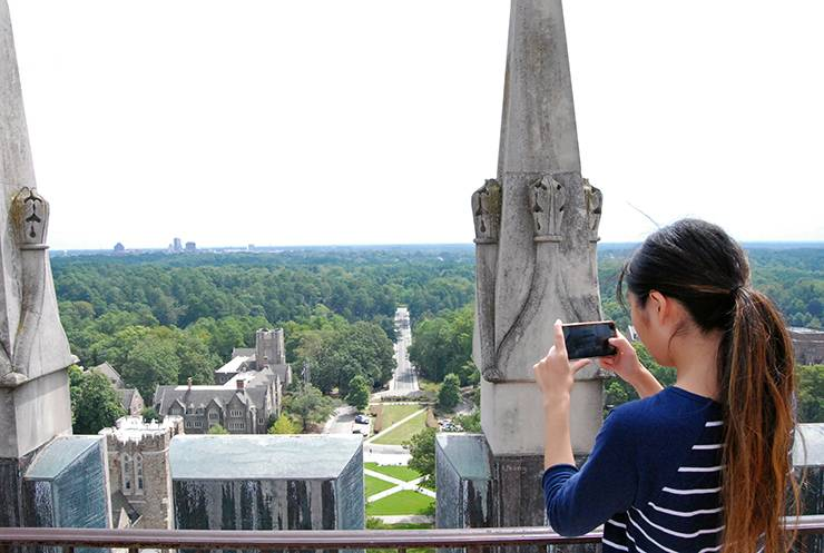 Duke student Annie Lu captures an image of the view from Duke Chapel on her phone.