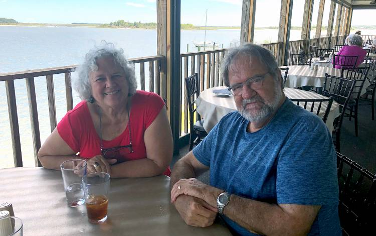 Diana Silimperi, left, and her husband Jos Muffels enjoy an outdoor lunch in Pamlico County last summer. Photo courtesy of Diana Silimperi.