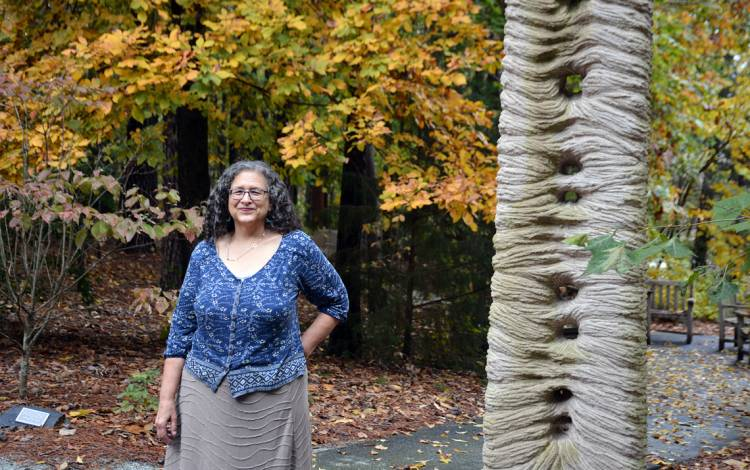 "Janet Silber stands next to the sculpture, ""Jacob's Ladder,"