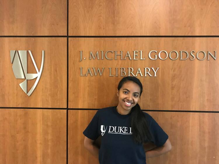 Fifaliana Ratodimahavonjy poses for a photo next to the J. Michael Goodson Law Library sign inside of Duke Law School