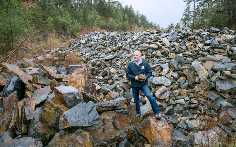 Paul Manning, director of Project Management for Duke's Facilities Management Department, holds a piece of stone at Duke's quarry outside of Hillsborough. Photo by Jared Lazarus, Duke Photography.