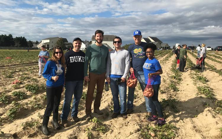 Matthew Barber (second from left) participated in a Yam Jam with Duke OB-GYN employees, students and families. They helped harvest sweet potatoes for the Society of St. Andrew.