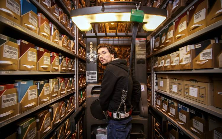Library Assistant Johnny Shanahan guides a lift high in the Library Service Center's stacks. Photo by Alex Boerner.