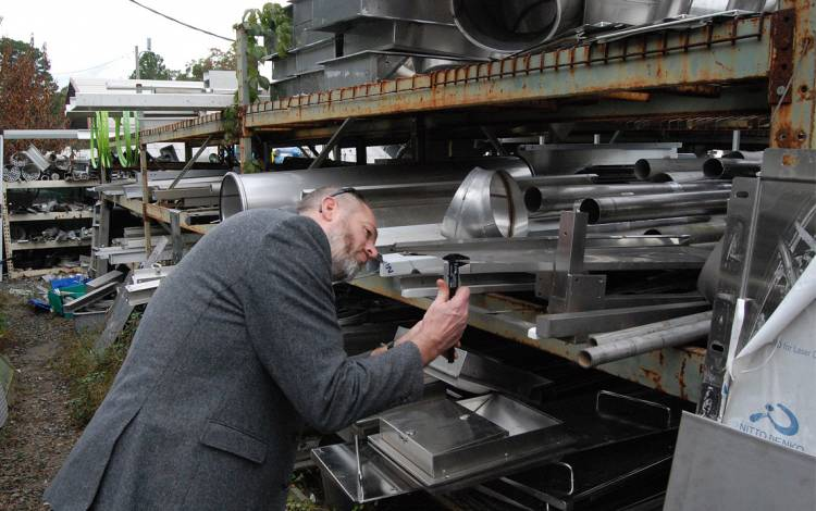 Chip Bobbert measures plates of steel at J & D Recycling. Photo by Stephen Schramm.