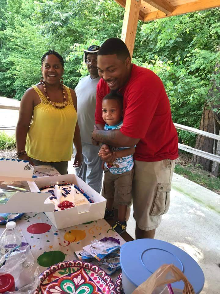 Le'Teya Robinson watches her husband and son blow out the candles on their birthday cake.