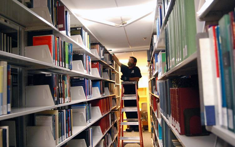 General Maintenance Mechanic Chip Meade fixes a light at Goodson Law Library. Photo by Stephen Schramm.