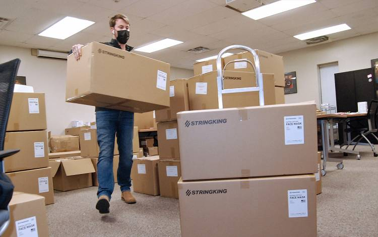 Justin Sharpe, associate director of the Student Wellness Center, loads boxes of face masks destined for the Fuqua School of Business. Photo by Stephen Schramm.