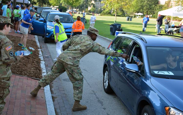 Duke Army ROTC members Amy Kramer and Raheem Adams hand out water to families as they wrap up packing Tuesday morning.