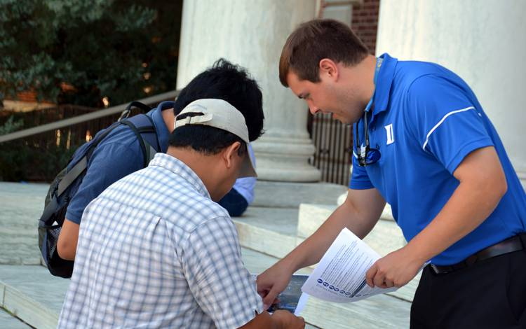 Admissions Officer Adam Tomasiello greets first years and families outside of the East Campus Union, where students picked up their move-in packet, DukeCard and mailbox keys.