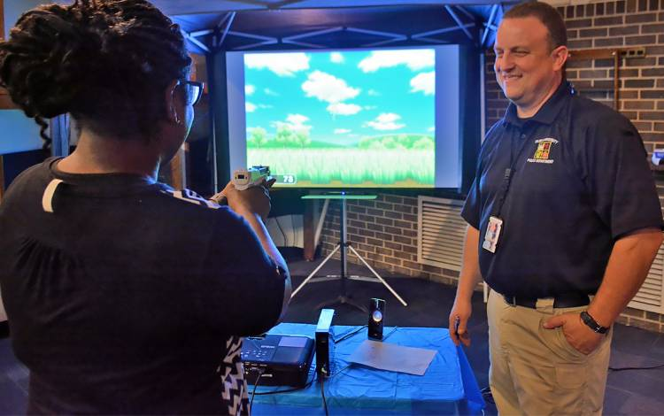 "Kelly George, a community services officer with Duke Police, plays Wii ""Duck Hunt"" with Duke Police Officer Lachanda Williams during National Night Out on campus. ""Trust me, I did terrible,"" Williams said after the game finished. The Wii challenge was one"