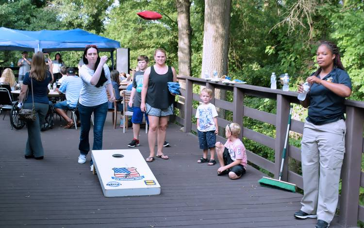 Ann Hale, a financial care counselor with Durham Gastroenterology Consultants and an alumna of Duke's Citizens' Police Academy, tosses a bag during cornhole. National Night Out also functioned as a reunion for Citizens' Police Academy, a six-week course t