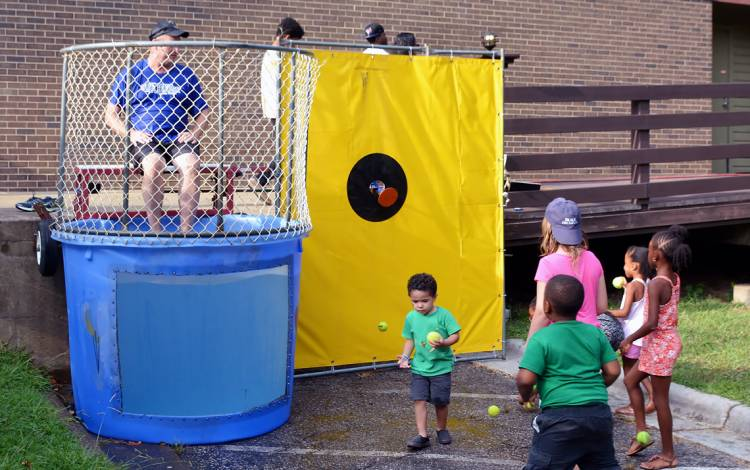 Duke Police Assistant Chief James Bjurstrom sits in the dunk tank as children prepare to take aim.