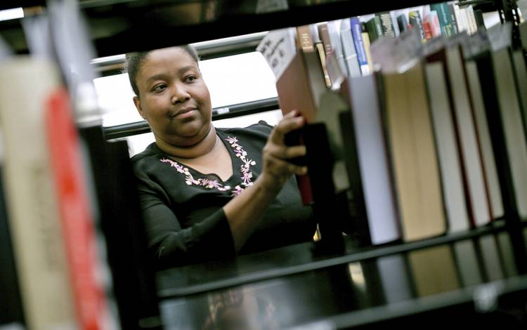 Senior Library Assistant Annette Tillery organizes books in Perkins Library. Photo by Jared Lazarus.
