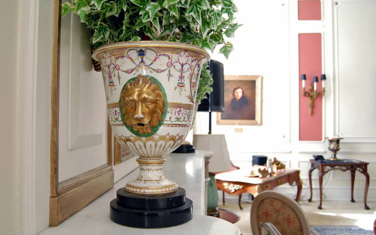 The Pink Parlor features shelves filled with antiques vases and artwork.