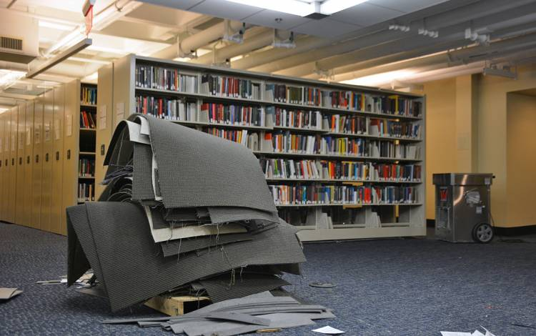 Stacks of old carpet rest next to shelves on Lower Level 2 in Perkins Library.