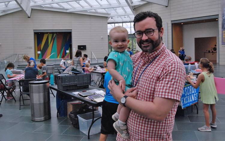 Ryan Helsel holds his daughter, Harper, in the Nasher Museum of Art's atrium.