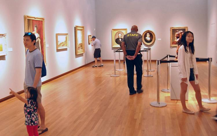 Gerald Gunnell, center, walks through the galleries, keeping an eye on the collection.