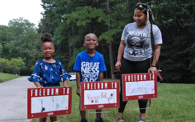Amare Harris, Chloe Robinson and Imani Nunn show off the yard signs they created.
