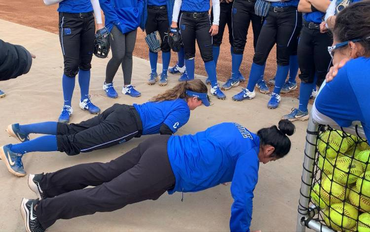 Student Raine Wilson, top, and softball coach Jessica Bracamonte, bottom, compete to do the most push-ups after a Duke Softball practice. Photo courtesy of Marissa Young.