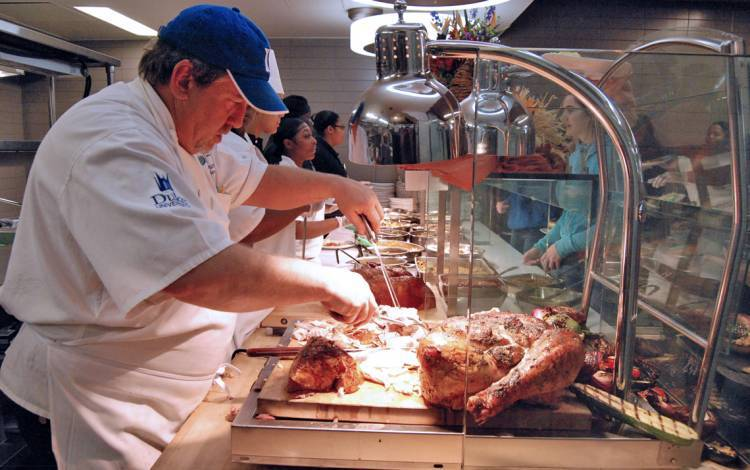 Executive Sous Chef Todd Dumke serves turkey during Duke Dining's Thanksgiving meal in 2019. Photo by Stephen Schramm.